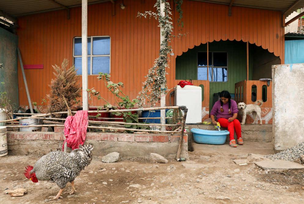 Leydi Condor habite le bidonville de Nueva Union. Elle lave ses vetêments devant sa maison à Lima, le 25 mai. Le quartier abrite des familles oubliées par l'État.