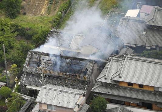 De la fumée s'élève d'une maison dans la province d'Osaka, quelques minutes après le tremblement de terre du 18 juin.