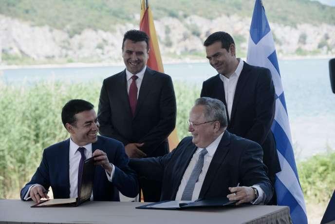 Le ministre grec des affaires étrangères, Nikos Kotzias (au premier plan, à droite), et son homologue macédonien, Nikola Dimitrov (au premier plan, à gauche), lors de la signature de l'accord instituant le nom de «République de Macédoine du Nord». A l'arrière-plan, les premiers ministres grec Alexis Tsipras (à droite) et macédonien, Zoran Zaev. Le 17 juin 2018, en Macédoine.