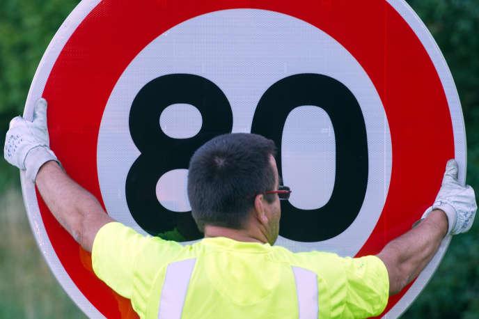 Un agent de la Direction interdépartementale des routes de l'Est (DIR Est) installe un panneau de limitation de vitesse.