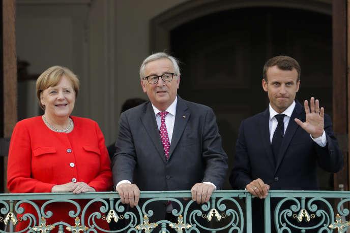 Angela Merkel et Emmanuel Macron, entourant le président de la Commission européenne Jean-Claude Junker, à Meseberg (Allemagne), le 19 juin.