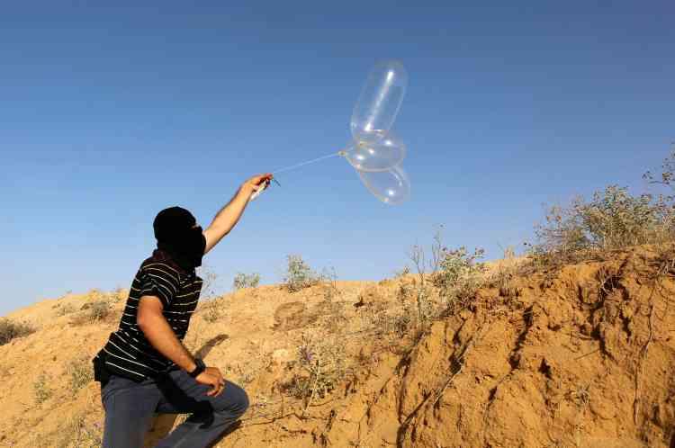 Un manifestant palestinien masqué lance vers Israël un ballon rempli d'hélium, à Rafah, le 17juin. Alors que le prix d'un cerf-volant est de 1dollar, celui d'un ballon n'est que de 50cents.