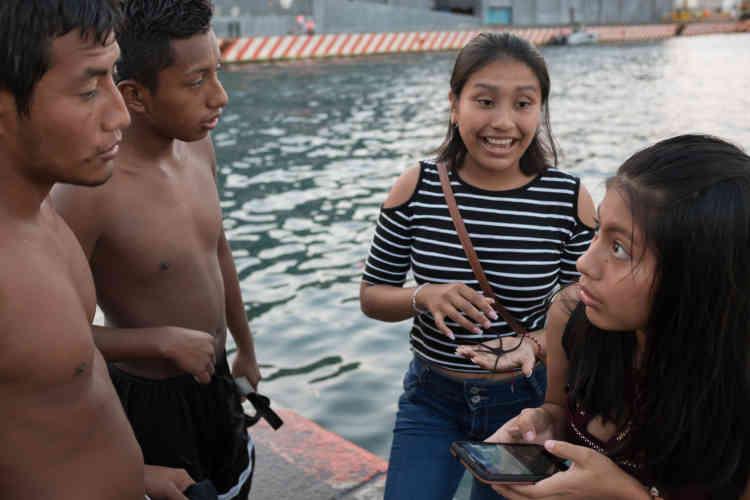 Des adolescents échangent leurs numéros de téléphone. Les garçons traquent les touristes sur le port.