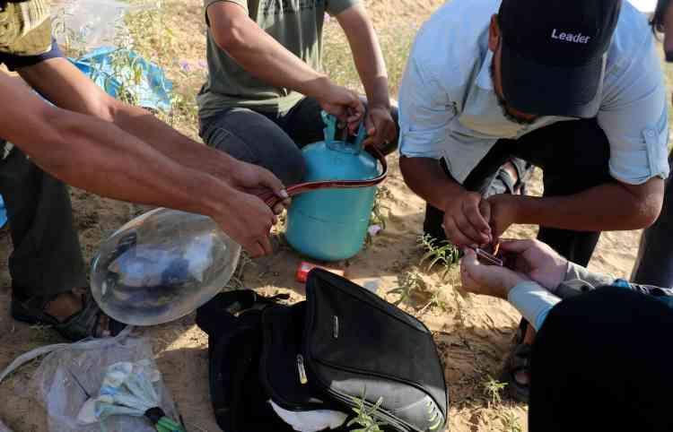 Des manifestants palestiniens injectent du gaz inflammable dans les ballons qu'ils feront voler vers Israël, à Rafah, le 17juin.