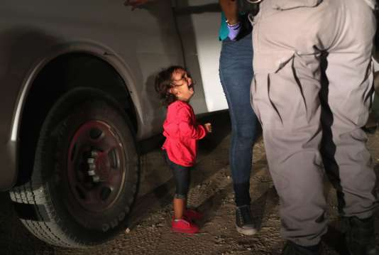 Photographie d'une petite Hondurienne en pull over rose de deux ans en pleurs pendant que sa mère se fait fouiller par la police aux frontières américaine dans la vallée du Rio Grande à la frontière avec le Mexique.