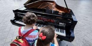 Des enfants jouent sur un piano installé dans la rue, dans le but de promouvoir la pratique musicale, à Valence (Espagne), le 11 mai.