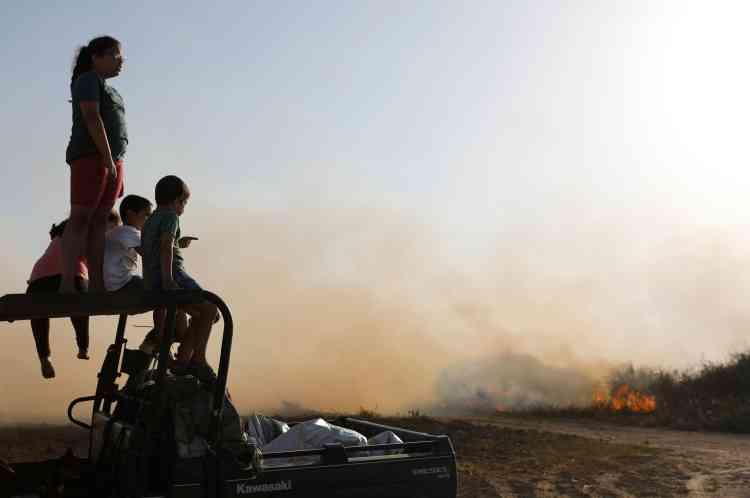 Des enfants israéliens regardent le feu causé par un cerf-volant enflammé au kibboutz Be'eri, près de la frontière, le 5 juin.