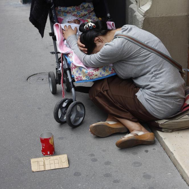 Une mère et son enfant faisant la manche sur un trottoir de Paris.
