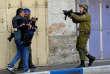 Des journalistes devant un soldat israélien lors d'affrontements dans les rues de Hébron, en Cisjordanie, le 15 décembre 2015.