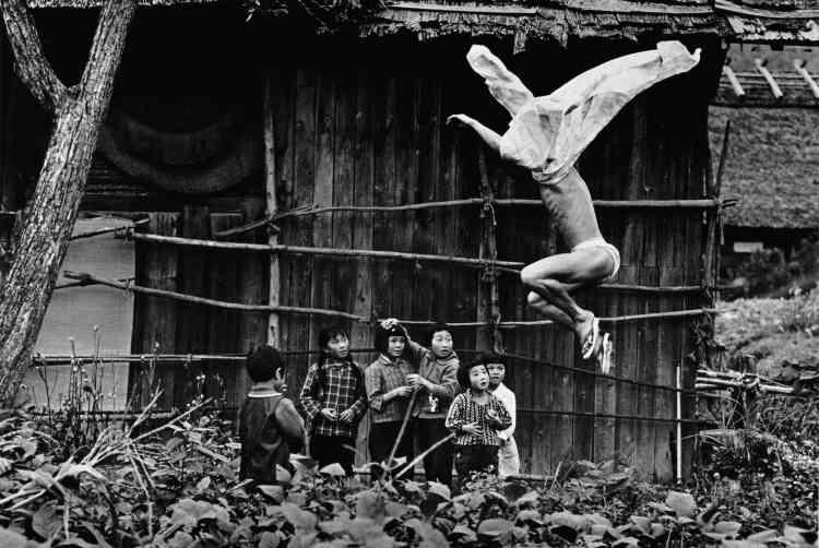 """«Cette photographie extraite de la série """"Kamaitachi"""" incarne le style photographique hybride de Hosoe, combinant performance et documentaire avec une esthétique dramatique et virile ‒ associée à celle de """"la danse des ténèbres"""" du danseur Hijikata qui a fortement influencé son art et l'a conduit à aborder la question du nu et de l'homosexualité. Travesti sous les traits d'un """"kamaitachi"""", démon légendaire qui hantait les rizières dans des paysages ruraux, Hijikata dévoile son corps d'athlète théâtralisé et adulé. » Aline Vidal"""