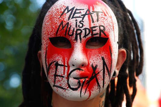Une femme portant un masque anti-viande lors d'une manifestation organisée par l'association L214 le 10 juin 2017 à Paris.