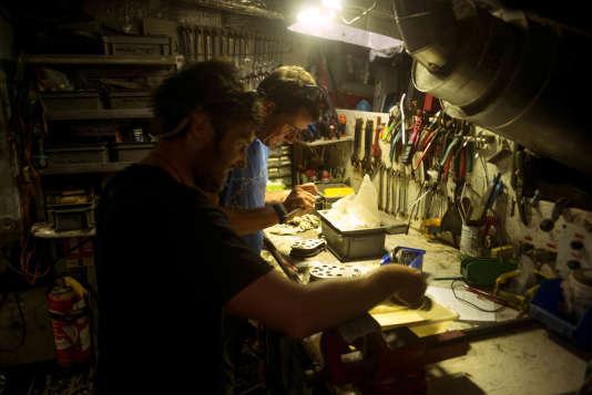 Le capitaine, Yohann Mucherie et Jonathan Lancelot réparent une poulie dans l'atelier du bateau.