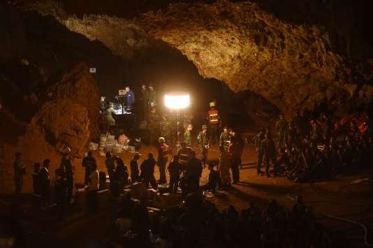 Des soldats thaïlandais mettent en place des installations électriques à l'intérieur de la grotte deTham Luang, le 26 juin 2018, alors que les opérations de recherche continuent.