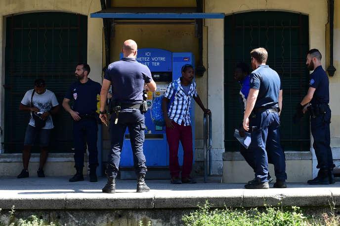 Des CRS contrôlent des migrants, à la gare de Menton, près de la frontière franco-italienne, le 14 juin.