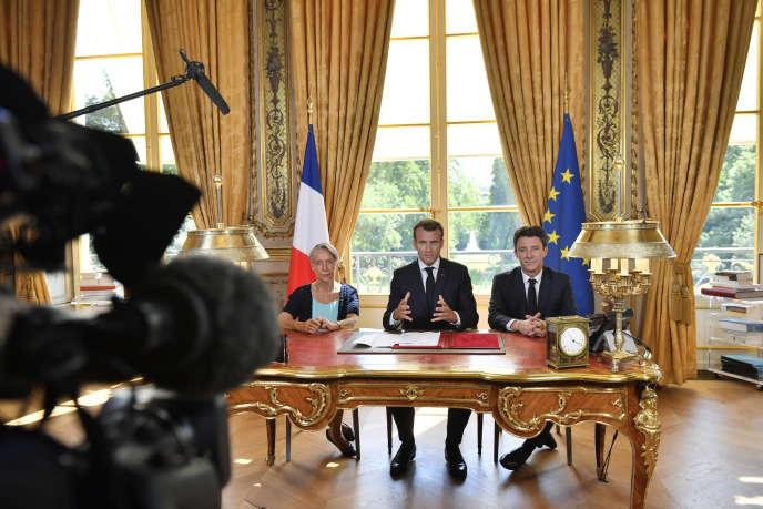 Flanqué de la ministre des transports Elisabeth Borne et du porte-parole du gouvernement Benjamin Griveaux, le président Emmanuel Macron a promulgué la loi réformant le ferroviaire, à l'Elysée à Paris, le 27 juin.