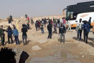 Sur cette photo datée du mardi 8 mai et fournie par le migrant libérien Ju Dennis, des migrants expulsés d'Algérie débarquent d'un bus dans le désert.