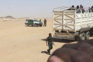 Des gendarmes algériens armés font monter des migrants dans des camions pour les déposer à la frontière du Niger.