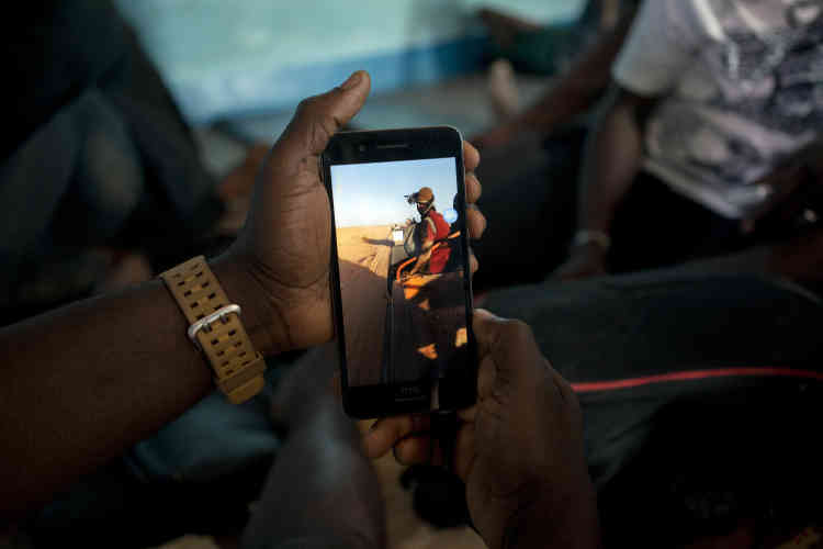Ju Dennis, originaire du Liberia, tient le téléphone portable avec lequel il a filmé son expulsion d'Algérie et qu'il a gardé caché.