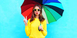 Fashion pretty cool woman holding colorful umbrella in autumn day over blue background wearing yellow knitted sweater