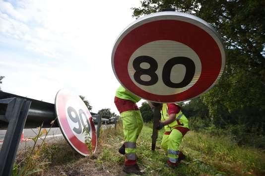 Des employés de la direction interdépartementale des routes de l'Est installent un panneau de limitation de vitesse à 80 km/h, le 29 juin à Wittenheim (Haut-Rhin).