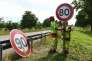 Employees of DIR Est (Direction interdepartementale des routes de l'Est) replace a 90 Km/h speed limit sign with an 80 Km/h one on a road on June 29, 2018 in Wittenheim eastern France. As of July 1, 2018 the speed limit on two lane roads from 90 KMPH to 80 KMPH, in the hope of addressing an alarming rise in the number of road deaths. / AFP / SEBASTIEN BOZON