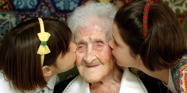 The World's oldest woman, Jeanne Calment, 120 years old, is kissed by two young girls during a special ceremony in a retirement home in Arles, Southern France, February 21, 1995.   REUTERS/Jean-Paul Pelisser/File Photo - TM3ECA50UFL01