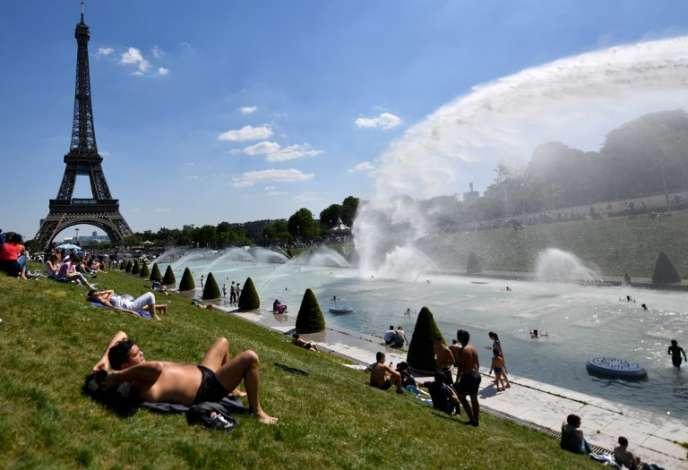 Des gens profitent du soleil et des fontaines du Trocadéro, à Paris, le 8 mai 2018.