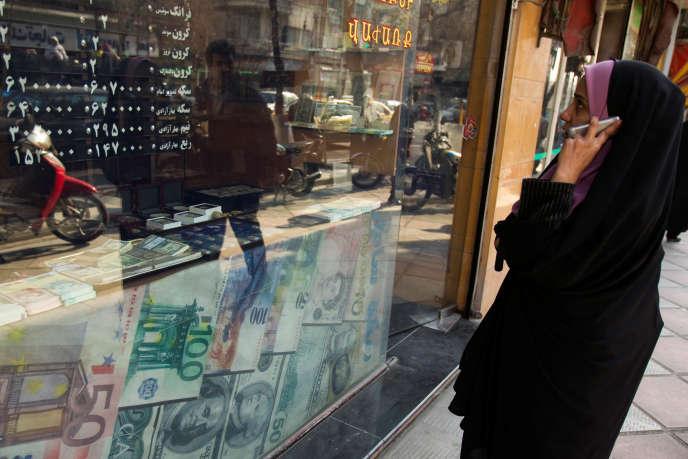 Une femme consulte les taux de change des devises, à Téhéran, en janvier 2012.