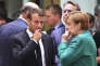 German Chancellor Angela Merkel, right, speaks with French President Emmanuel Macron during a round table meeting at an EU summit in Brussels, Thursday, June 28, 2018. European Union leaders meet for a two-day summit to address the political crisis over migration and discuss how to proceed on the Brexit negotiations. (AP Photo/Geert Vanden Wijngaert)