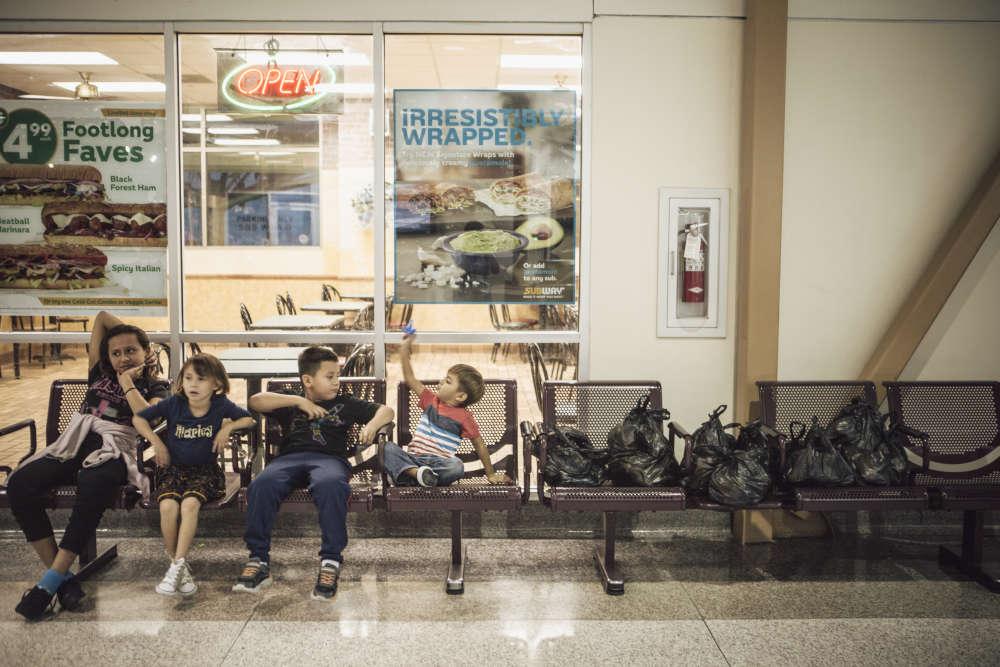 Des enfants salvadoriens, à la gare de bus de McAllen. Sur le banc, des sacs de nourritureet autres produits de première nécessité donnés aux migrants par Catholic Charities.« Les gens entreprennent ce voyage, malgré tous les dangers, pour de vraies raisons »,estimesœur Norma, bénévole de l'organisation caritative.