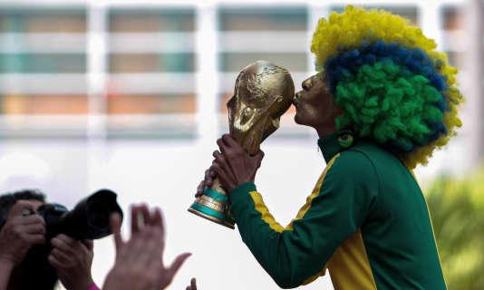 Un fan du Brésil embrasse une réplique de la Coupe du monde, le 2 juillet à Sao Paulo.
