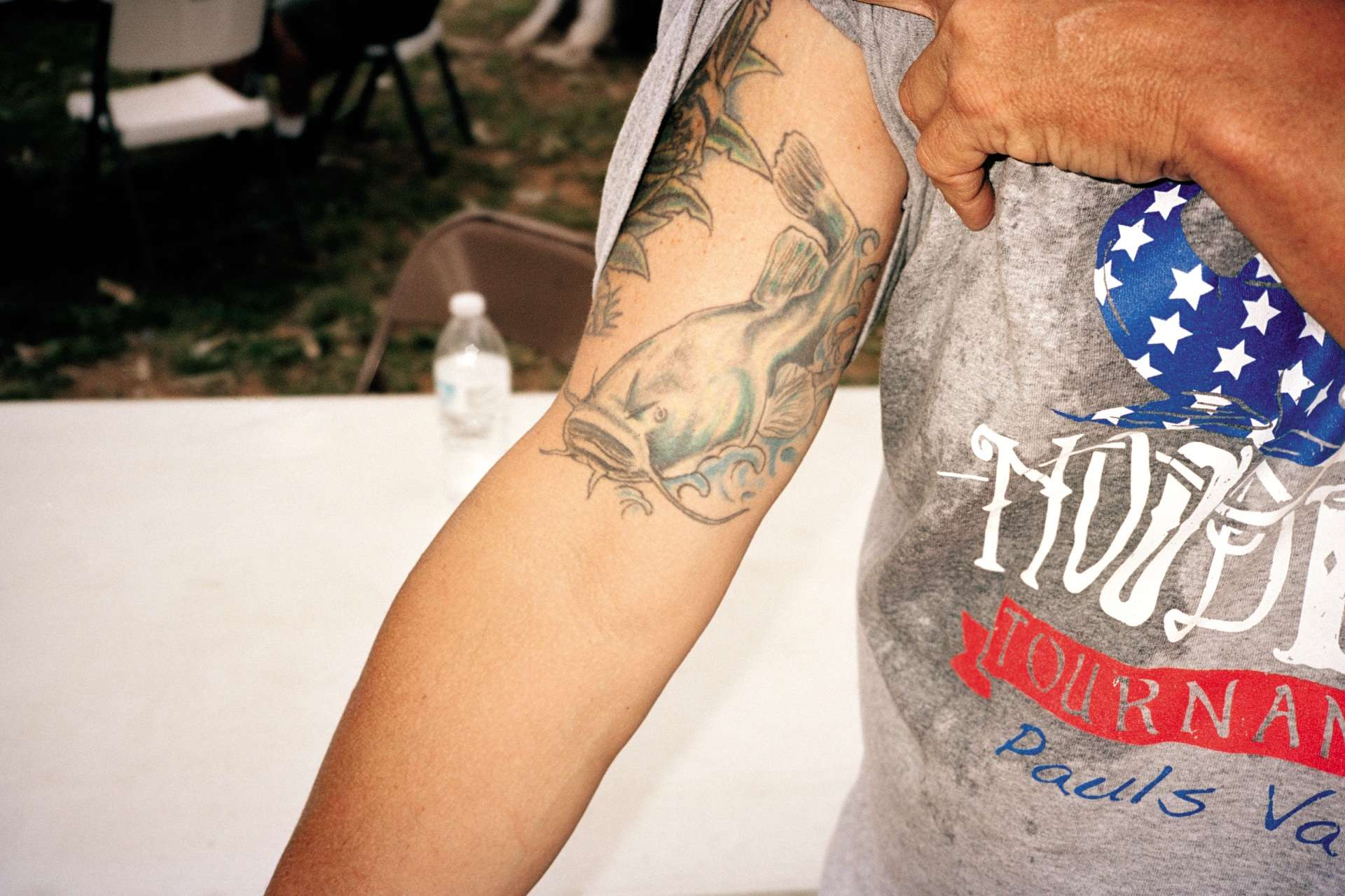 Un spectateur du Okie Noodling Tournament exhibe son tatouage représentant un poisson-chat.
