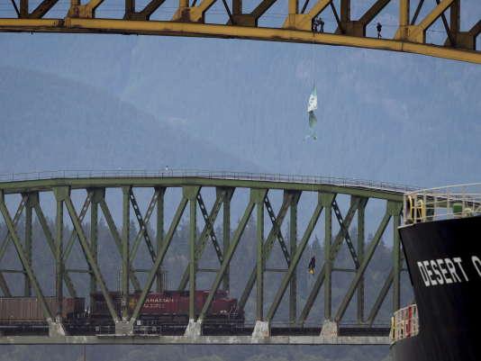 Les militants écologistes ont déroulé des câbles mardi3juillet au matin sous la structure d'acier du pont de Vancouver pour s'y installer et déployer de longues oriflammes, bloquant ainsi le passage des cargos.