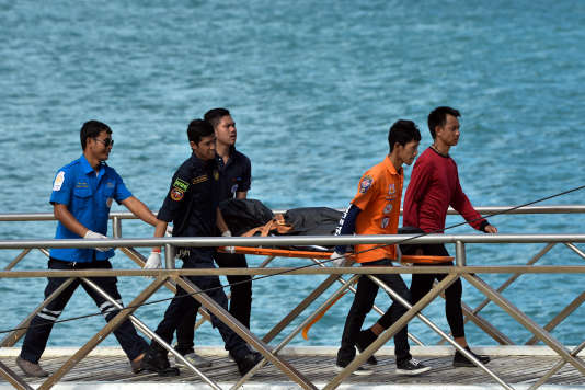 Des secours thaïlandais portent le corps d'une victime repêchée en mer le 6 juillet, après le nauvrage du «Phoenix» au large de Phuket.