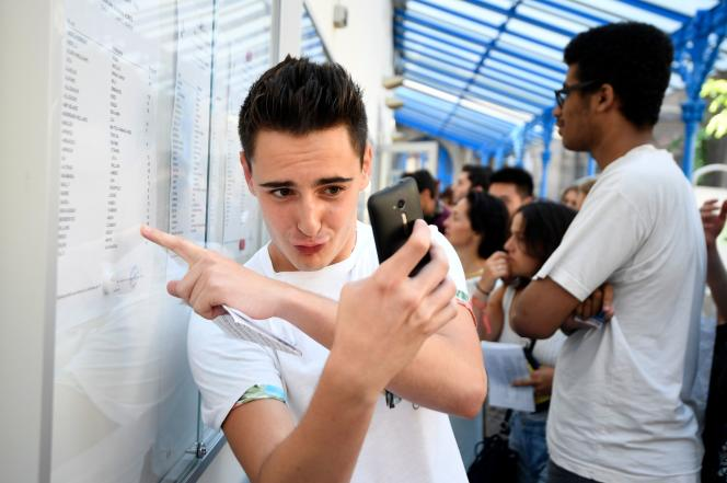 A student poses with a smartphone as he reacts with others after receiving their baccalauréat examination results at a lycee in Paris on July 6, 2018.  End of the suspense for the 750,000 baccalaureate candidates: the results have begun to arrive, bringing as every year their share of emotions, between relief, joy and disappointment. / AFP / Eric FEFERBERG