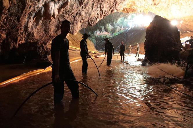 L'équipe de sauvetage installe une pompe à eau à l'entrée de la grotte où sont coincés douze adolescents et leur entraîneur, depuis le 23 juin.