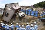 Des sauveteurs recherchent des survivants dans les ruines d'une maison. Les records de précipitations ont provoqué des glissements de terrain àKumano, dans la préfecture d'Hiroshima au Japon, 9 juillet 2018.