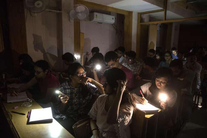Coupure de courant au centre de soutien scolaire Vidya Guru, dans le nord de Delhi. Les étudients travaillent à la lueur de leurs téléphones portables.