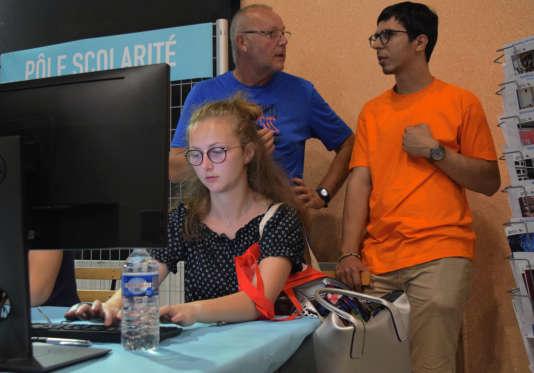 Laura procède à son inscriptionen ligne en première année de sciences du langage. Derrière elle, son père et un jeune discutent.