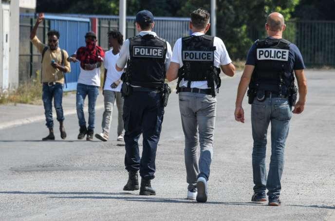 Des policiers marchent près de personnes migrantes, à Calais, le 8 juillet.