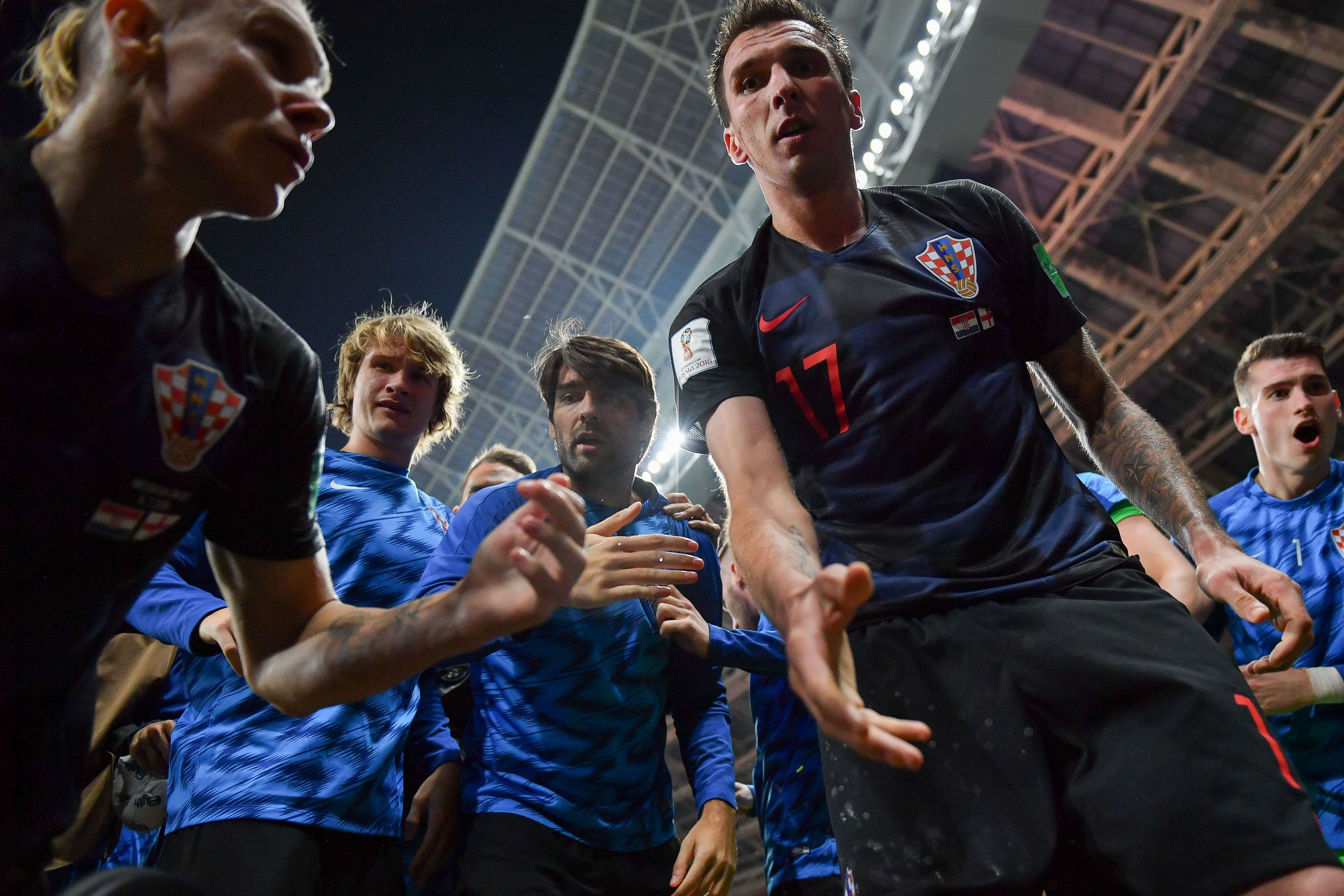 TOPSHOT - Croatia's forward Mario Mandzukic (C) offers to help AFP photographer Yuri Cortez after he fell on him with teammates while celebrating their second goal during the Russia 2018 World Cup semi-final football match between Croatia and England at the Luzhniki Stadium in Moscow on July 11, 2018. RESTRICTED TO EDITORIAL USE - NO MOBILE PUSH ALERTS/DOWNLOADS / AFP / Yuri CORTEZ / RESTRICTED TO EDITORIAL USE - NO MOBILE PUSH ALERTS/DOWNLOADS