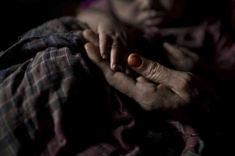 «S» tient la main de son petit garçon, dans leur abri du camp de réfugiés de Kutupalong, au Bangladesh.