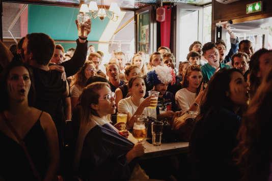 Des supporteurs regardent la demi-finale de la Coupe du monde autour d'unepinte de bière, au Downtown Café, à Paris le 10 juillet.