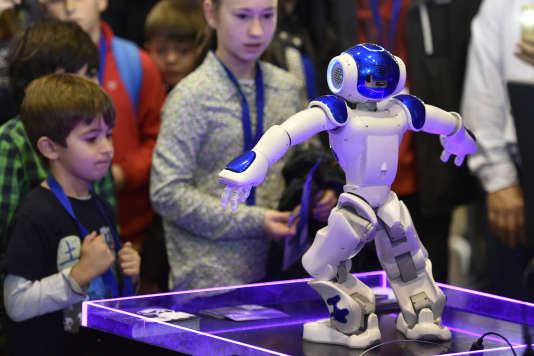 Les enfants regardent Nao,un robot humanoïde programmable développé par la société de robotique française Aldebaran Robotics lors de la Global Robot Expo à Madrid, le 31 janvier 2016.