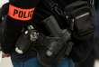 A photo taken on March 1, 2017 shows the service weapon, handcuffs and armband of a plainclothes police officer Calais. / AFP PHOTO / PHILIPPE HUGUEN