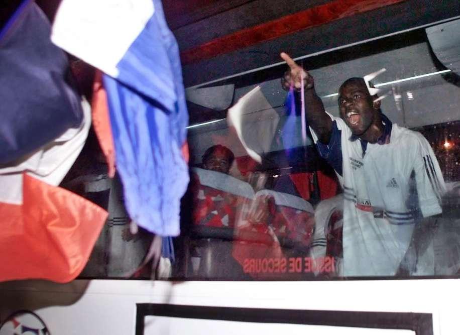 Lilian Thuram salue les supporteurs depuis le bus transportant les Bleus à Clairefontaine.