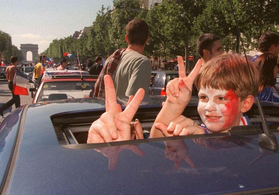 Un enfant maquillé aux couleurs de la France fait le signe de la victoire avenue des Champs-Elysées, à Paris.