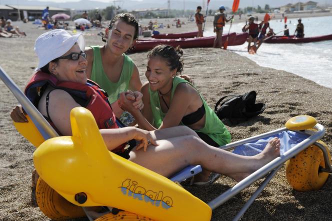 Des jeunes volontaires s'occupent d'une femme handicapée sur la plage du Prado, à Marseille, dans le cadre de leur service civique.
