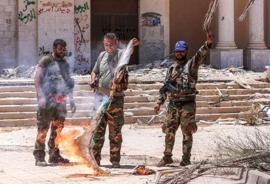 Des soldats de l'armée syrienne brûlent le drapeau de l'opposition, près de la frontière avec la Jordanie dans la province de Deraa, le 7 juillet.