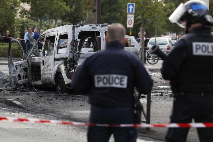 Des policiers près de la carcasse brûlée d'une voiture de police, le 8 octobre 2016, àViry-Châtillon.